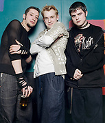 Three young punk rockers standing together and posing.