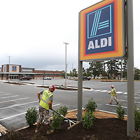 Sportsman Lawn and Landscape employee Chase Lowe, left, begins to spread out mulch to complete the landscaping around the new Aldi grocery store on North Gloster in Tupelo.