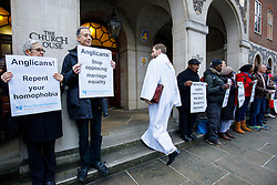 © Licensed to London News Pictures. 15/02/2017. London, UK. Choir singers walk past whilst LGBT Campaigners, including Peter Tatchall, hold a protest vigil outside the General Synod of the Church of England, where same sex marriage is due to be debated. Photo credit: Tolga Akmen/LNP