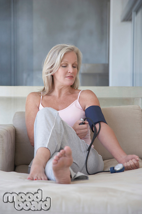 Mature woman sitting on sofa barefoot checking blood pressure with sphygmometer
