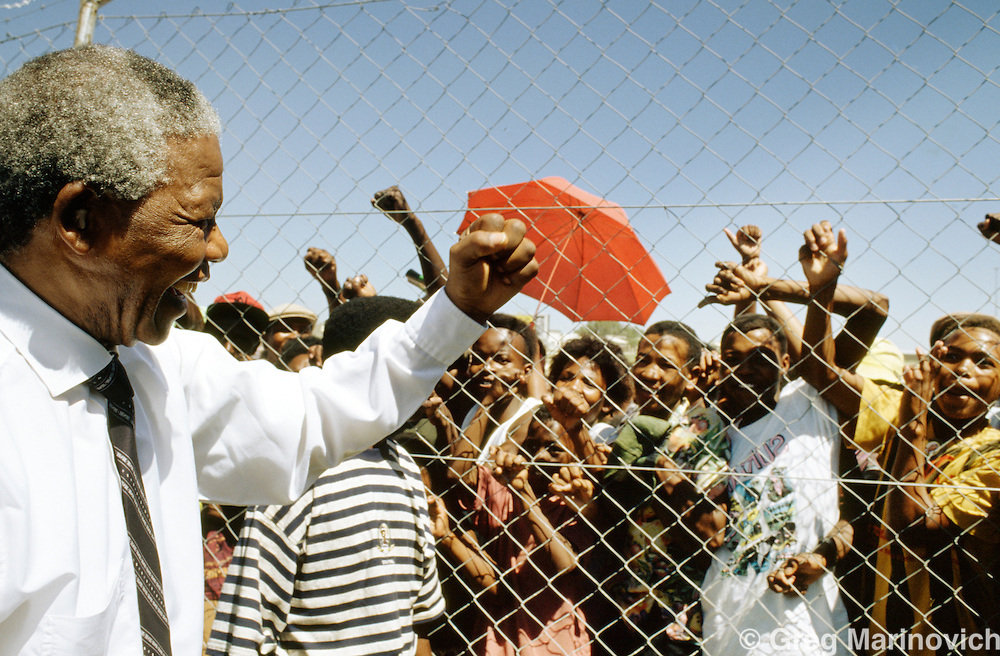 Nelson Mandela, ANC leader greets a crowd at a stadium  shortly before elections.  South Africa. 1994