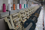 Sewing machines, print a sequin design on a bio cotton T-shirt at Pratibha Syntax factory, where organic cotton is being used to make clothes, Indore, India.