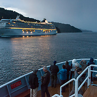 Guests on the bow of the National Geographic Sea Lion watch a large cruise ship pass by on the Georgia Strait on the Inside Passage of British Columbia, Canada.