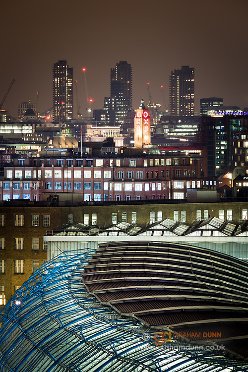 The curved roof of Waterloo Station, with the Oxo Tower and the Barbican tower blocks in the distance. A London urban landscape captured at night from an elevated viewpoint. February. 2016