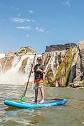 "Boy give ""hang loose"" sign while S.U.P Boarding at high water below the impressive Shoshone Falls, Twin Falls, Idaho."