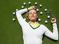 Woman Lying on Putting Green with Golf Balls