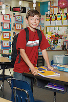 School boy standing in classroom