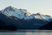 A snow covered mountain towers over Duffy lake, on the Sea to Sky Highway , British Columbia, Canada