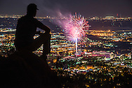 A man watching 4th of July fireworks over Folsom Field above Boulder, CO. ©Brett Wilhelm