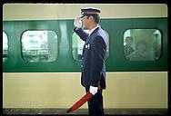 Green & yellow stripes of bullet train frame stationmaster as he salutes for departure;Utsunomiya Japan