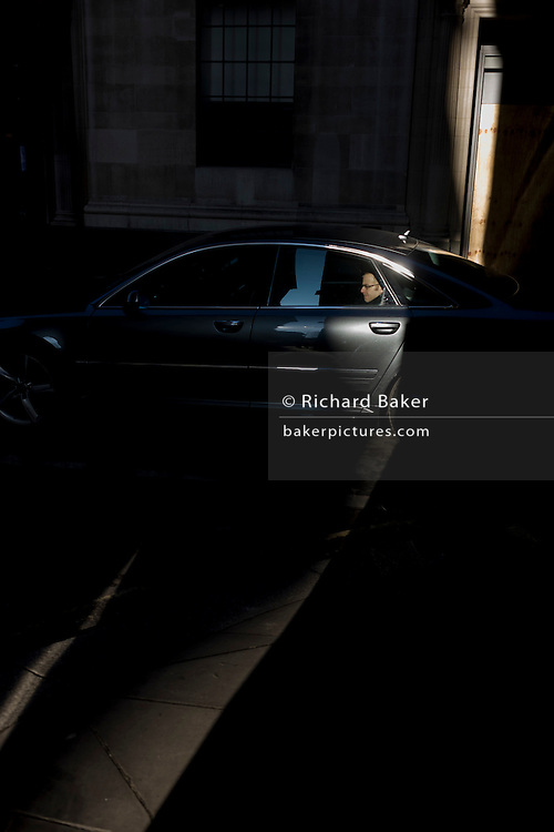 A passenger in the rear seat of a courtesy car is caught in a shaft of early spring light in a side street in the capital's financial district. This is Lombard Street, originally a piece of land granted by King Edward I to goldsmiths from the part of northern Italy known as Lombardy (larger than the modern region of Lombardy). It is a narrow and usually dark sidestreet near the Bank of England in the heart of what is called the Square Mile - the inner-part and oldest quarter of London occupied first by the Romans 2,000 years ago. Nowadays the City of London is home to banks and financial institutions but also with a resident population of under 10,000 but a daily working population of 311,000.