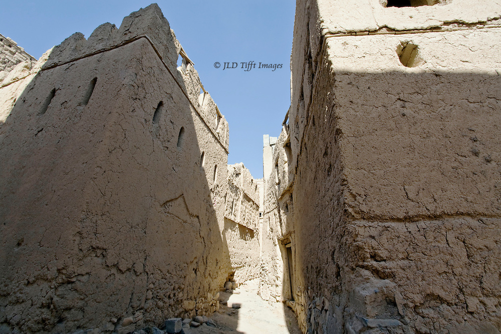 Sunlit alley between shadowed mud brick mansions, village of Al Hamra, Oman.  The homes have been abandoned but remain standing.  All are defensive with small slit windows set high in the facades, and crenellations on the flat roofs.