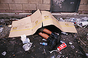 The morning after: a drunken youth sleeping amid trash covered with cardboard during the yearly wine festival in Logroño, La Rioja Region, Spain.