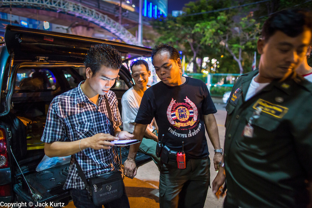 "10 NOVEMBER 2012 - BANGKOK, THAILAND:  A Ruamkatanyu Foundation emergency response team waits for a call near the Ekamai BTS stop during a Saturday night shift. The Ruamkatanyu Foundation was started more than 60 years ago as a charitable organisation that collected the dead and transported them to the nearest facility. Crews sometimes found that the person they had been called to collect wasn't dead, and they were called upon to provide emergency medical care. That's how the foundation medical and rescue service was started. The foundation has 7,000 volunteers nationwide and along with the larger Poh Teck Tung Foundation, is one of the two largest rescue services in the country. The volunteer crews were once dubbed Bangkok's ""Body Snatchers"" but they do much more than that now.     PHOTO BY JACK KURTZ"