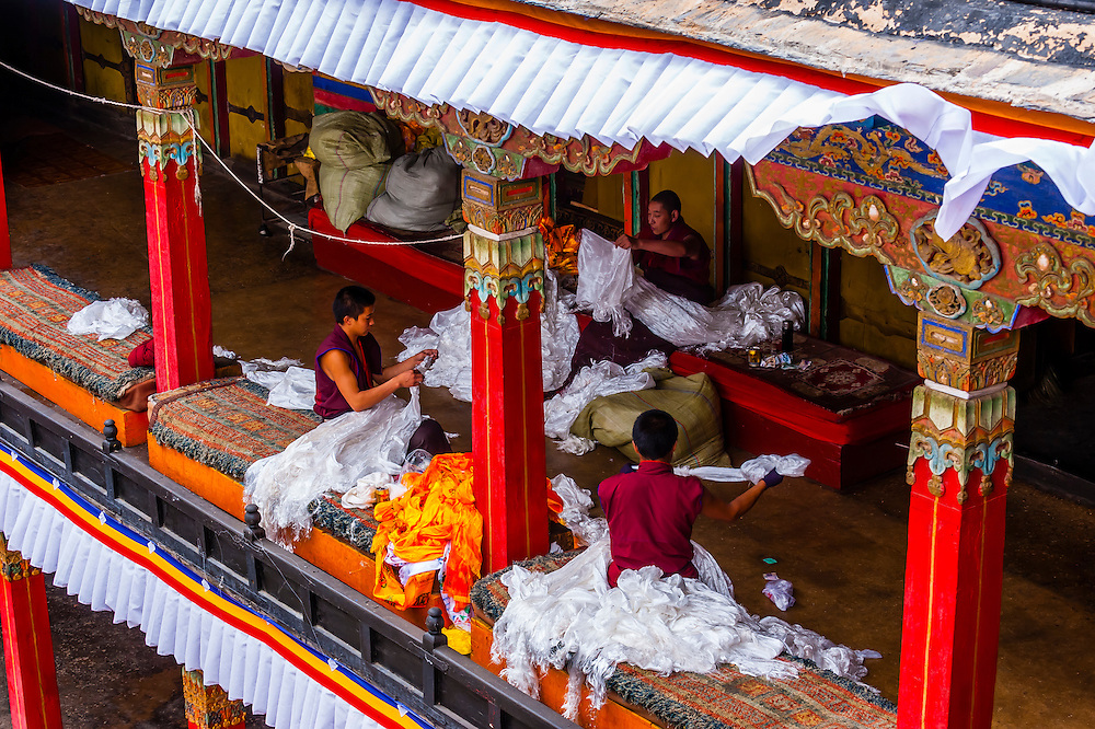 Buddhist monks sorting khatas (traditional ceremonial scarfs), Tashilhunpo Monastery, Shigatse, Tibet (Xizang), China.