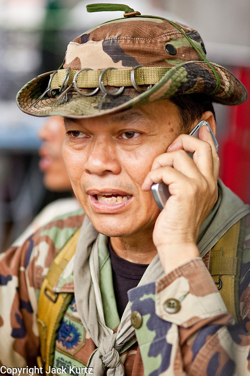 "May 12 - BANGKOK, THAILAND: Maj. Gen. KHATTIYA ""Seh Daeng"" SAWASDIPOL uses a cell phone to stay in touch with Red Shirt barricades in the Red Shirt camp in Bangkok Wednesday. Seh Daeng, as he is known, has emerged as the Red Shirts unofficial military commander. He has organized the barricades that ring the Red Shirt camp and has threatened to organize a guerilla campaign against the government if the Red Shirt protest is crushed by force. Seh Daeng is a hero to many Thais because he is credited with crushing Thailand's communist insurgency in the 1970's and 80's. He was the commander of Thailand's Internal Security Operations Command but after his political activities became apparent he was made the head aerobics instructor for the Thai army. He is now seen as one of the major personalities destabilizing the country and the government alleges that he is behind many of the grenade attacks and drive by shootings directed at government buildings and officials and he is wanted for a long list of felony offenses including weapons charges and terrorism related charges. Although some Red Shirts have officially repudiated him, he is still frequently seen around the Reds' barricades. The army has started proceedings to fire him, but he remains a general on active duty.   Photo by Jack Kurtz"