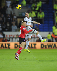 Swansea City's Angel Rangel battles for the high ball with Cardiff City's Craig Bellamy - Photo mandatory by-line: Joe Meredith/JMP - Tel: Mobile: 07966 386802 03/11/2013 - SPORT - FOOTBALL - The Cardiff City Stadium - Cardiff - Cardiff City v Swansea City - Barclays Premier League