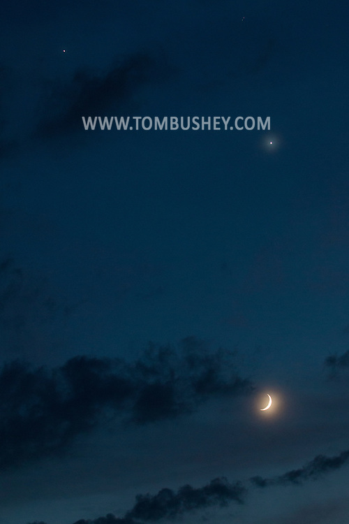 Middletown, New York - The crescent moon and the planets, Venus, above the moon, and Jupiter, at left,  shine in the night sky on June 19, 2015.