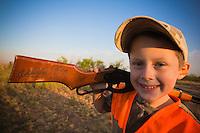 YOUNG BOY WEARING BLAZE ORANGE AND HOLDING A RED RIDER BB GUN