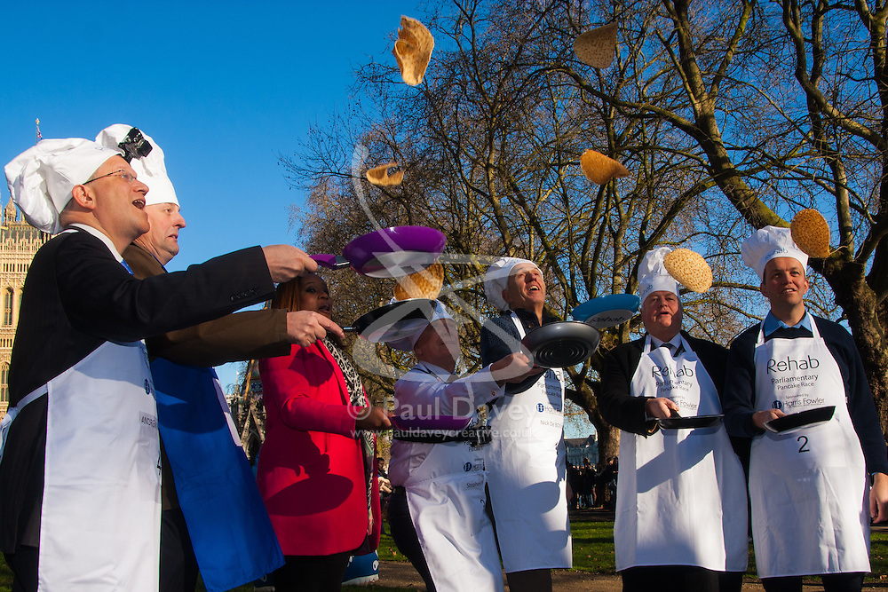 London, February 17th 2015. Members of Parliament put their dignity aside for a bit of fun as they compete in the annual Parliamentary Pancake Race in Victoria Tower Gardens adjacent to the House of Lords.  PICTURED: Left to right, Andrew Rosindell, Lord Redesdale, ITV News Presenter and official race starter Charlene White, Stephen Pound, Nick DeBois, Lord Kennedy, David Burrowes practice tossing their pancakes.