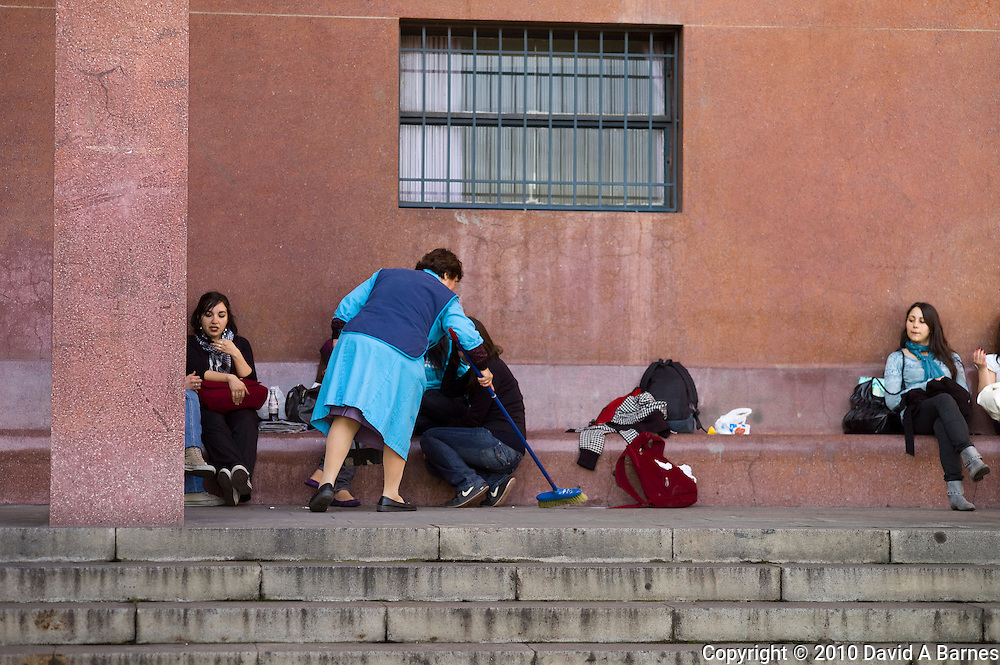Woman sweeping around university students relaxing, Santiago, Chile