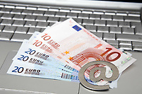 euro bills with the arobase e-mail sign on a laptop computer