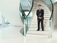 Confident Businessman holding folder standing on stairs