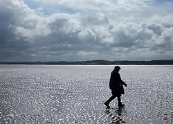 © Licensed to London News Pictures. 07/04/2012. Stiffkey, UK People walk under stormy skies on the salt marshes at Stiffkey, Norfolk today 7th April 2012.  Weather is expected to deteriorate over the next two days Photo credit : Stephen Simpson/LNP