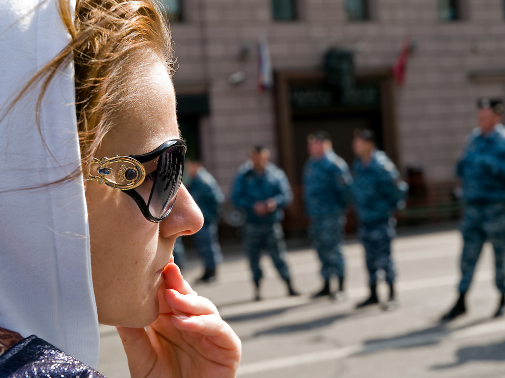 Junge Frau mit Sonnenbrille an der - von russischen Spezialeinheit OMON (OMOH) abgesperrte Prachtstraße Twerskaja - vor dem Beginn der größten Militärparade in Rußland seit Ende der Sowjetunion 1991 (9.Mai 2008). <br /> <br /> Young woman with sunglasses at a street blocked by the Russian Special Purpose Police Squad OMON shortly before the Victory Day parade started (took place the 9th of May 2008) which showcased military hardware for the first time since the Soviet collapse.