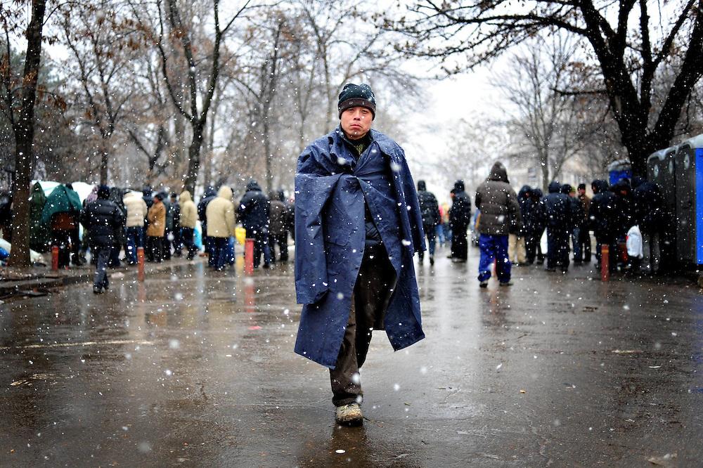 Un cetatean chinez trece pe langa corturile amplasate in fata Ambasadei Chinei la Bucuresti, vineri, 20 februarie 2009. Cateva sute de chinezi si-au facut o tabara peste drum de ambasada Republicii Chineze la Bucuresti, dupa ce au fost concediati de catre companiile la care lucrau in Romania. BOGDAN MARAN / MEDIAFAX FOTO