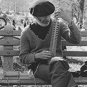 """Man playing a """"Chapman Stick"""" guitar-like instrument on a bench in Central Park, 1978"""