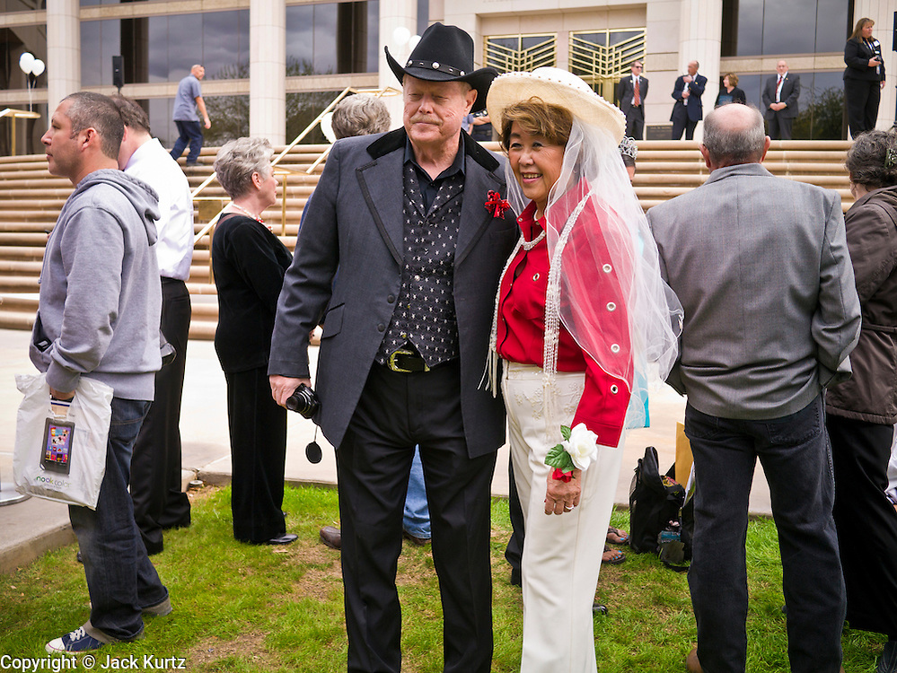 14 FEBRUARY 2012 - PHOENIX, AZ:   RICH PARTAIN and his fiance, MIMI WONG, wait, along with other couples, for their wedding to start in front of the Arizona Supreme Court. Ninetysix couples got married in a mass ceremony on the steps of the Arizona Supreme Court to mark the Valentine's Day holiday. The wedding was also an occasion to mark Arizona's centennial of statehood.     PHOTO BY JACK KURTZ