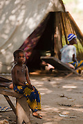 A boy sits on a bench in a spontaneous settlement near the village of Kpoto, Benin on Tuesday October 26, 2010. Almost all of the village's 1500 people have moved to a location near the local church, located about 500 meters away, where they now live in basic shelters.