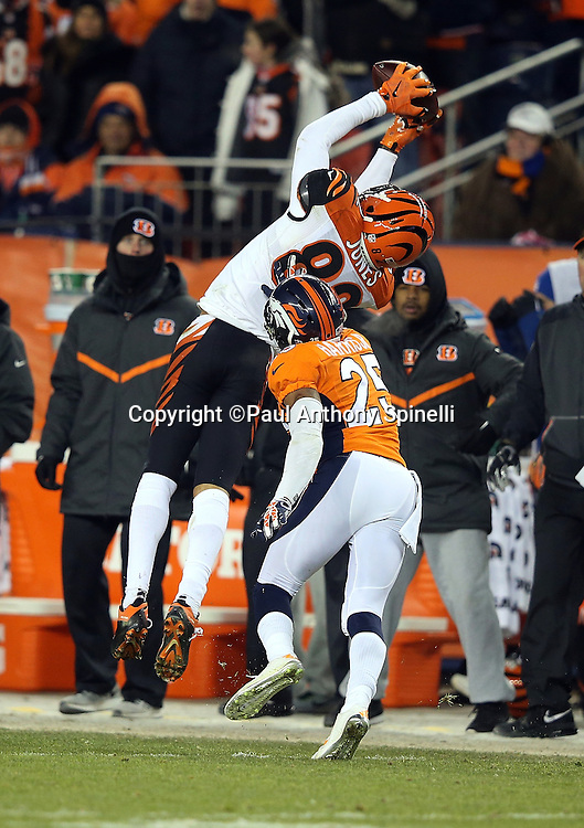 Cincinnati Bengals wide receiver Marvin Jones (82) leaps and catches a third quarter pass at mid-field while covered by Denver Broncos cornerback Chris Harris, Jr. (25) during the 2015 NFL week 16 regular season football game against the Denver Broncos on Monday, Dec. 28, 2015 in Denver. The Broncos won the game in overtime 20-17. (©Paul Anthony Spinelli)