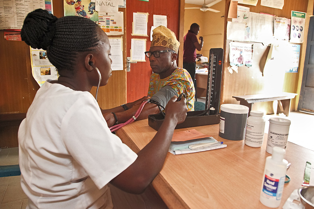 INDIVIDUAL(S) PHOTOGRAPHED: Adetona Olubunmi (left) and Hon Wale Ogundim (right). LOCATION: Ikeja Primary Health Care Center, Lagos, Nigeria. CAPTION: A nurse at the Ikeja Health Center takes the blood pressure of retired administrator Hon Wale Ogundim.