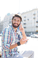 Smiling man looking away while using cell phone in city
