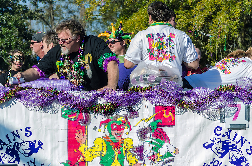 A reveler with Cain's Jolly Jesters reaches down to pass a beer to a parade goer as his float travels down Canal Street in downtown Mobile, Ala., during the Joe Cain Procession at Mardi Gras, March 2, 2014. French settlers held the first Mardi Gras in 1703, making Mobile's celebration the oldest Mardi Gras in the United States. (Photo by Carmen K. Sisson/Cloudybright)