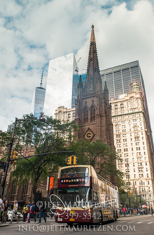 A bus drives beneath the Trinity Church and One World Trade Center, both of which at one time were the tallest buildings in NYC.