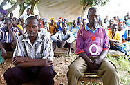 Oculokori, Uganda: Former LRA rebel Samuel Ogwal, left, and former LRA commander David Amar, right, sit with neighbors during a meeting in their tiny village in northern Uganda. As young boys, Ogwal and Amar were abducted by Joseph Kony's Lord's Resistance Army (LRA) and  forced to teach children to kill and to watch them die, to deliver beatings and conduct ritualistic murders. They are now facing a new kind of terror: returning home to the uncertain judgment of family and friends who had been brutalized by rebels like them. (PHOTO MIGUEL JUAREZ LUGO)