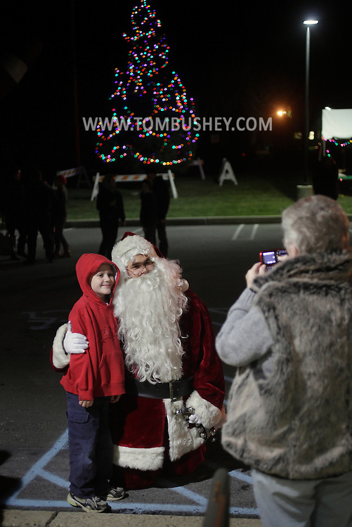Town of Wallkill, New York - A child poses for a photograph with Santa Claus after the holiday tree lighting at Town Hall on Nov. 26, 2011.