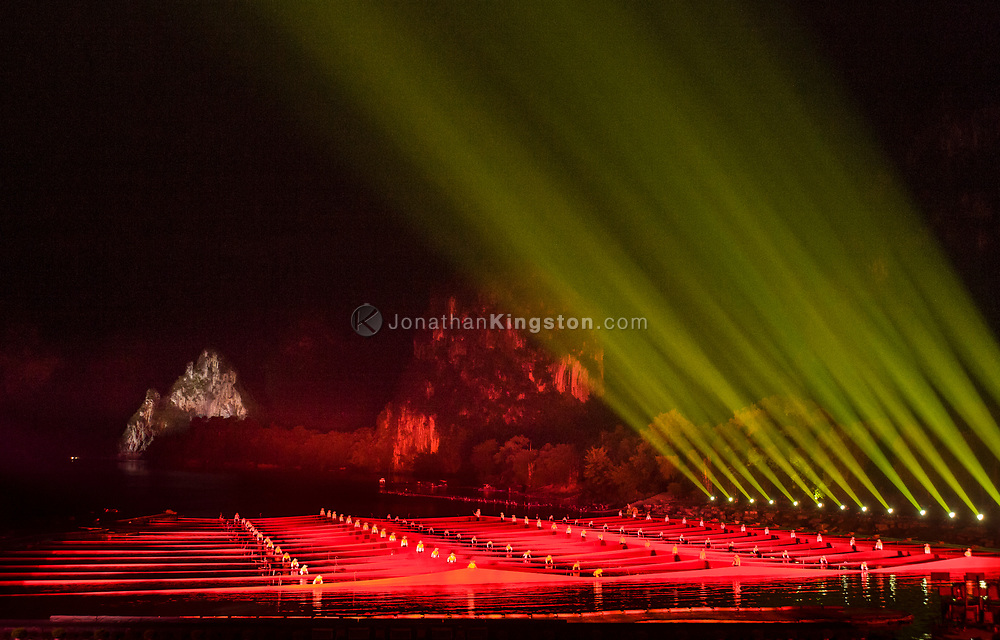 Green stage lights illuminate the night sky above performers in the Liu Sanjie light show titled The Impression, in an outdoor theater at night in Yangshuo, China.