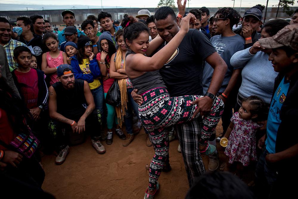 """Carla Estefany Ávila 23, originaria de Tegucigalpa, baila """"perreo"""" con Rogelio Redondo, 37, originario de Trujillo, en el medio del campo de béisbol del campamento de Tijuana, Estado de Baja California, México. 21/11/2018<br /> <br /> A mediados de octubre 2018, miles de migrantes hondureños abandonaron sus casas para emprender el viaje hasta los Estados Unidos, recorriendo casi 5.000 kilómetros hasta la ciudad fronteriza de Tijuana en menos de dos meses.<br /> Las 10.000 personas (según estimaciones de la UNCHR) que conformaron la caravana visibilizaron el fenómeno migratorio por primera vez en Centroamérica, denunciando las problemáticas de extrema pobreza y violencia presentes en los lugares de origen."""