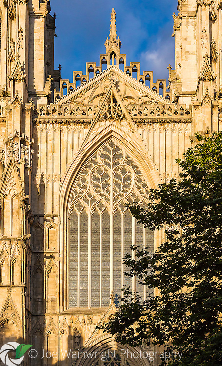 The magnificent structure of York Minster, North Yorkshire. The West Front illuminated by warm evening light. The towers were built between 1438 and 1472, with the Great West Window added about a century earlier in the 1330s.