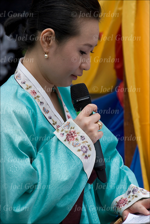 Korean speaker reading from notes at the Lotus Lantern Festival in Union Square Park, New York City.
