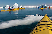 Kayaking off Petermann Island, home to the southernmost breeding colony of gentoo penguins, located below the Lemaire channel, near the Antarctic penninsula