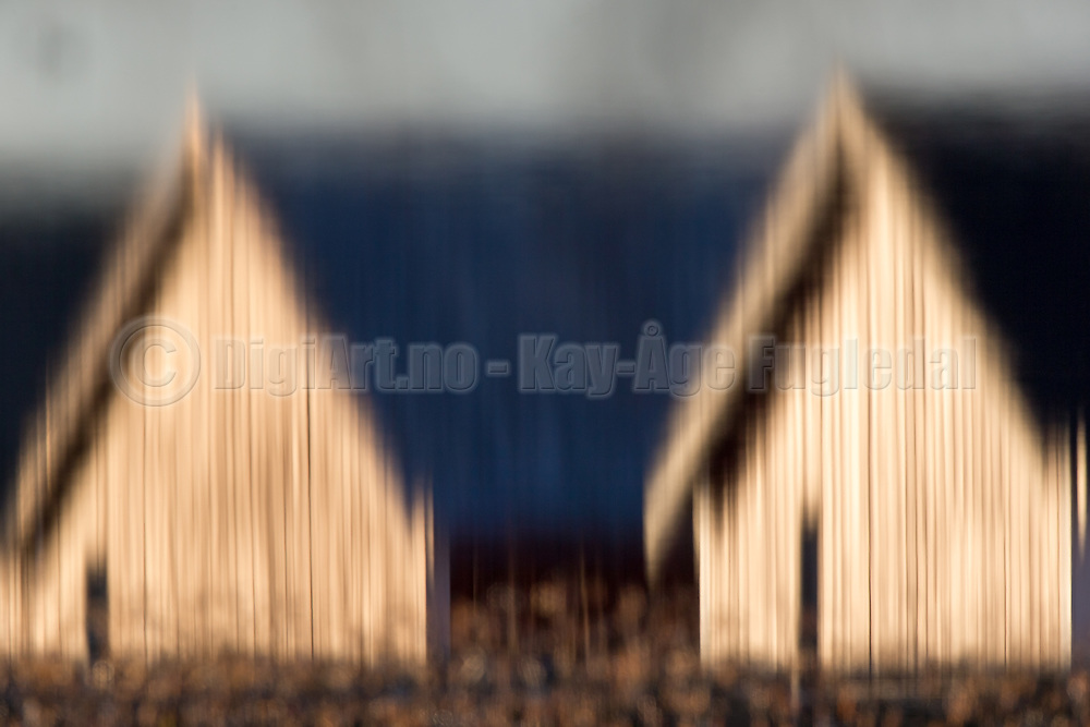 Two boathouses photograped through water, then mirrored | To naust som er fotografert via vann, og derettter speglet.