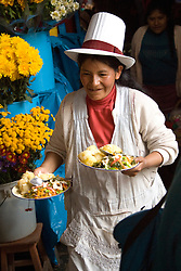 Woman serving plates of food in market, Cuzco, Peru, South America