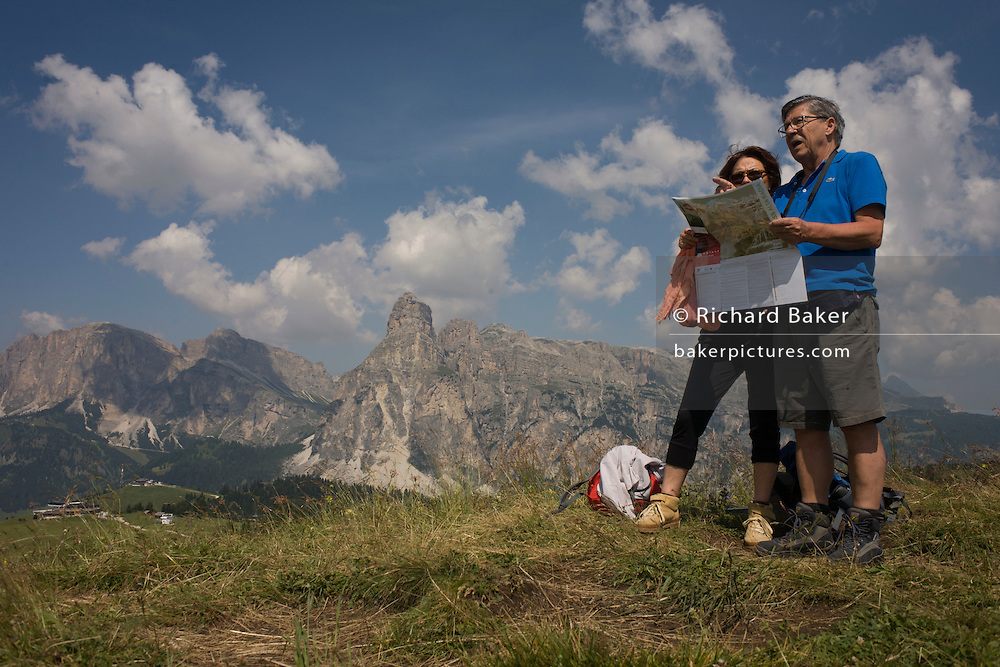 Hiking couple consult their map with panoramic views of mountain tops behind in the Pralongià above San Cassiano-St. Kassian in the Dolomites, south Tyrol, northern Italy. In winter, the Pralongià meadows are the heart of Alta Badia's skiing area.