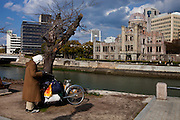 Homeless man reading a newspaper in Hiroshima's Peace Memorial Park. In the background the A-Bomb Dome.