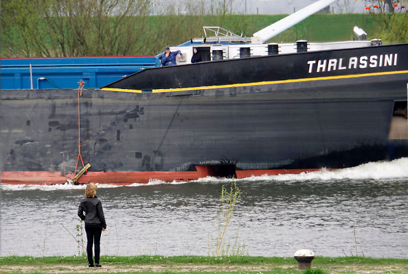 Nederland, 13-4-2018 Een leeg binnenvaartschip vaart over de Maas richting Limburg en Belgie. Op de wal kijkt een vrouw toe.Foto: Flip Franssen